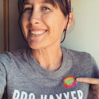 """White Woman With Brown Hair Wearing A Grey """"pro-vaxxer"""" Shirt And Pointing To A Colorful Sticker On That Shirt."""